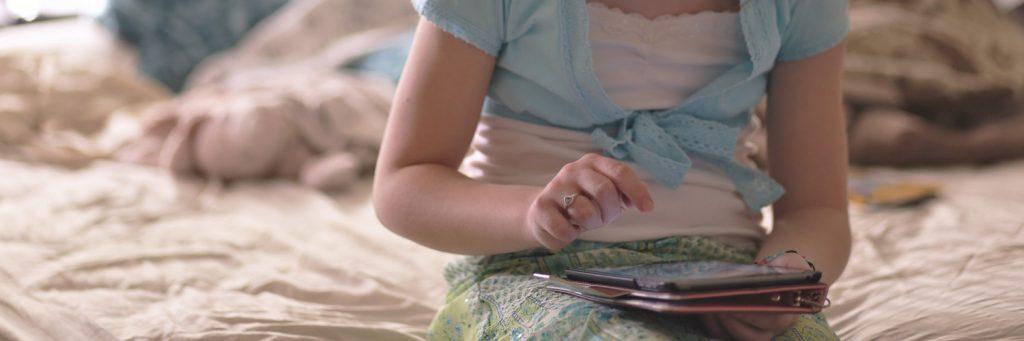 nena navegant amb tablet sobre el llit