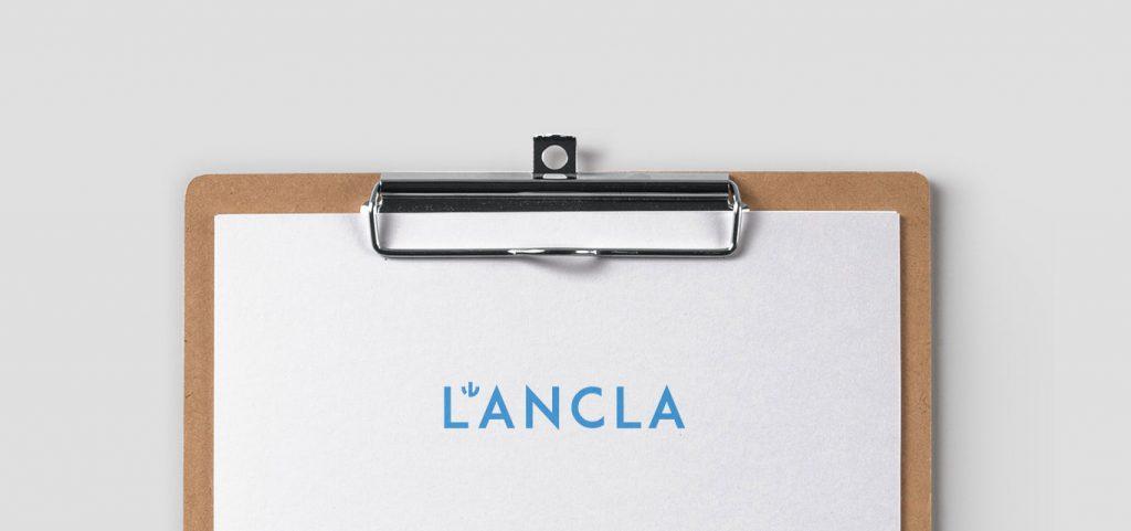 logo modern de botiga de banyadors de color blau sobre suport de paper i fusta