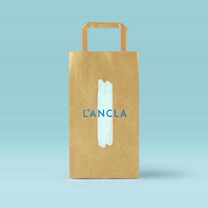 bossa de cartó de botiga de banyadors amb logo i pinzellada turquesa