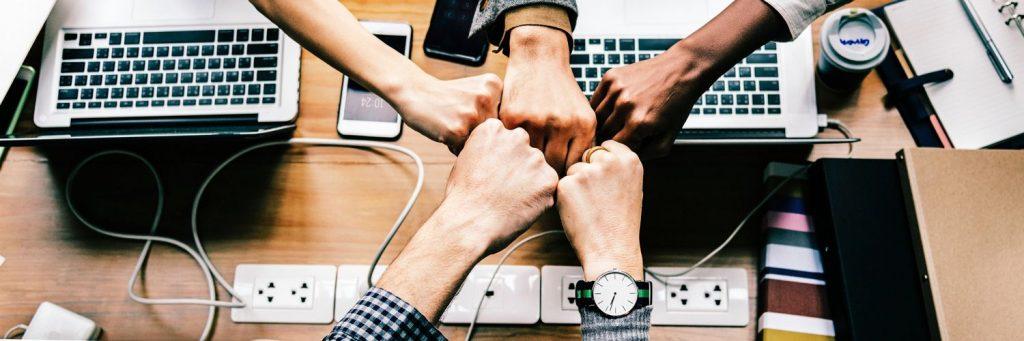 mans juntes sobre ordinadors i taula de fusta