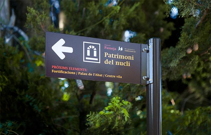 disseny de senyalització de patrimoni de cartell vertical-explicatiu amb pictogrames i fons marro a la natura